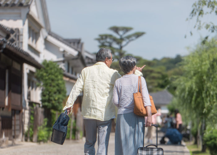 A couple carrying luggage and walking through a scenic destination