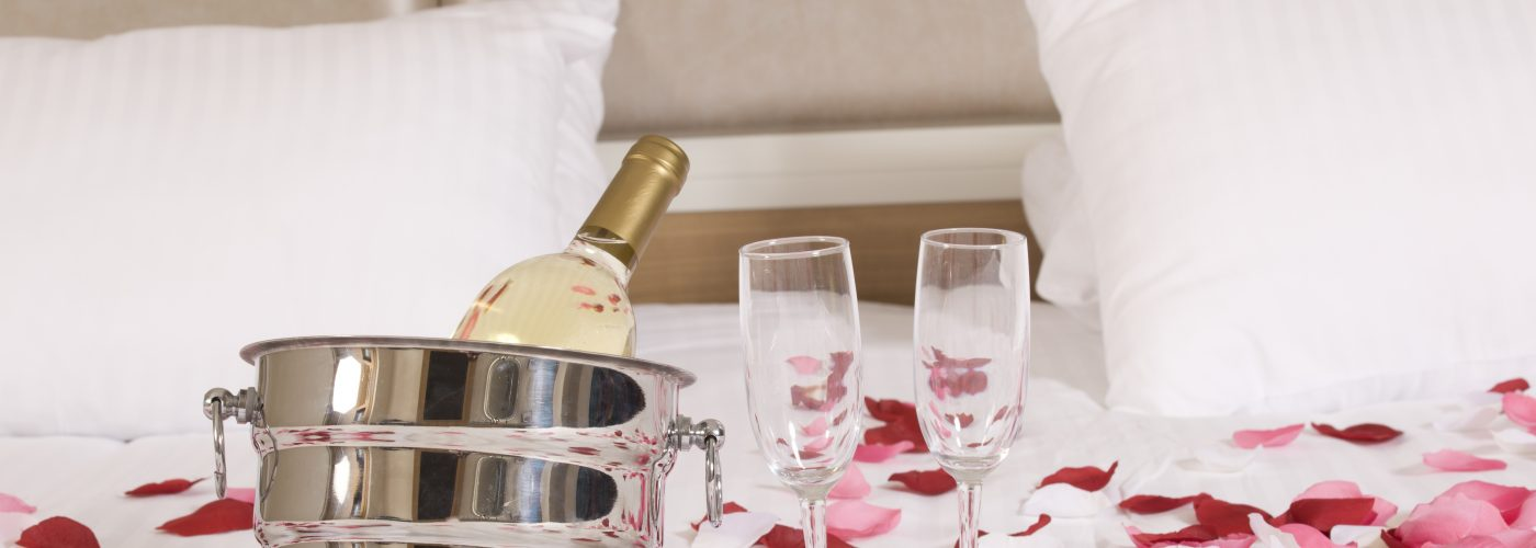 hotel bed with roses and sparking wine
