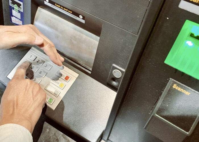 foreign transaction fees photo of person covering PIN number on ATM.