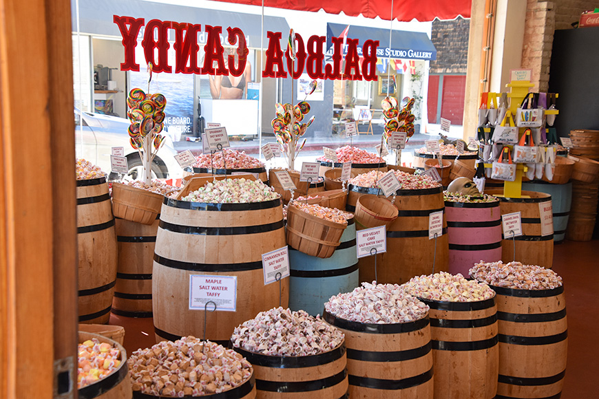 View Of the interior of the Balboa Candy Shop showing wooden barrels taffy and huge lolly pops near the front window