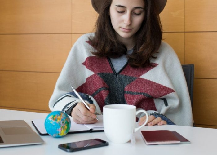 young-girl-in-a-poncho-sitting-at-her-desk-planning-out-her-trip-in-her-diary