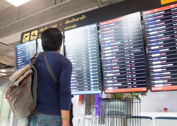 man looking at airport screens.