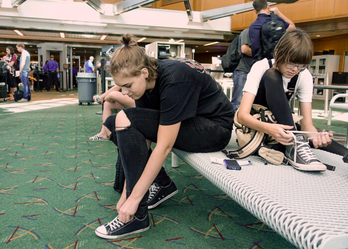 Travelers put their shoes back on after clearing airport security