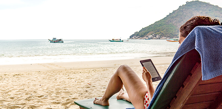 woman reading her kindle on a beach