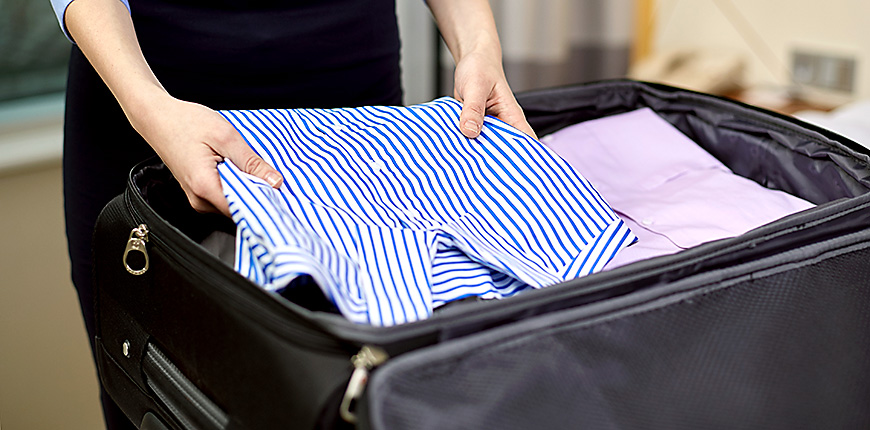 businesswomen packing blouses into a suitcase
