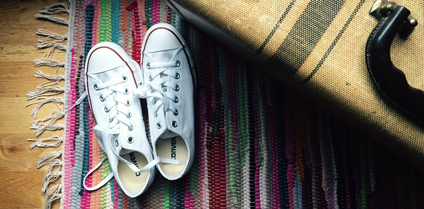 pair of converse sneakers next to a suitcase