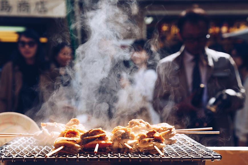 grilled seafood scallop and sea urchin eggs skewer with smoke, japanese street food at tsukiji fish market
