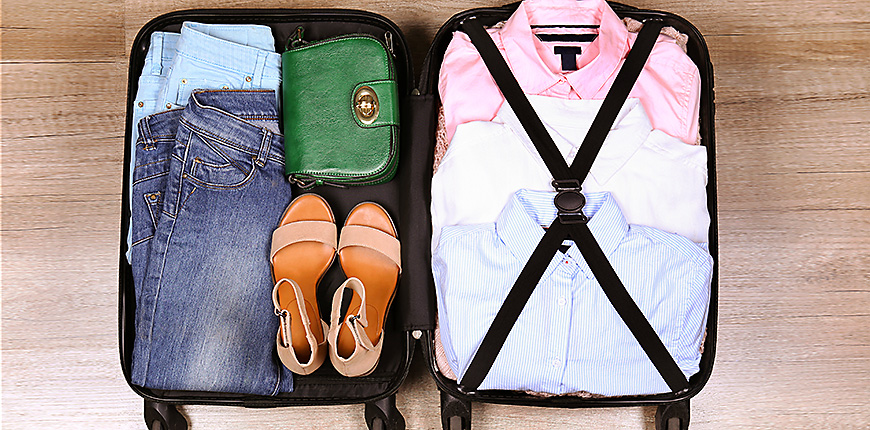 Open suitcase fully packed with folded women's clothing