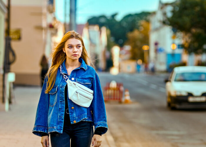 girl in a denim jacket and waist bag walks through the city along the road