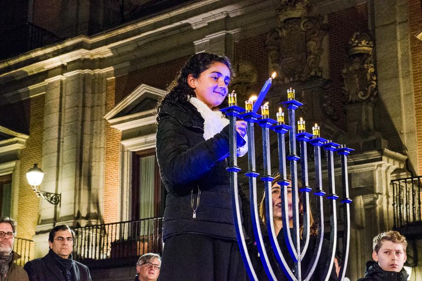 A young girl and the luna alfon (r), director of ibn gabirol estrella toledano school, lighting candles during hanukkah celebration