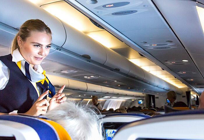 flight attendant speaking with passengers on flight plane