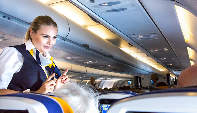flight attendant speaking with passengers on flight plane