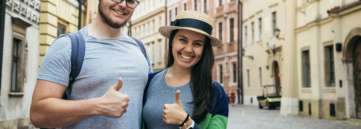 cheerful couple stand with thumb up at old european street