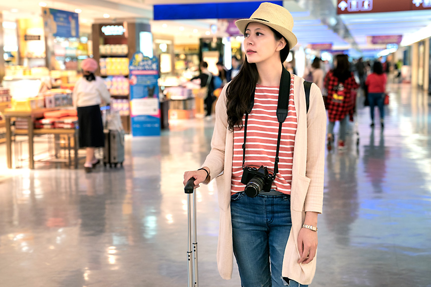 woman wearing a red striped shirt and hat stands at the airport.