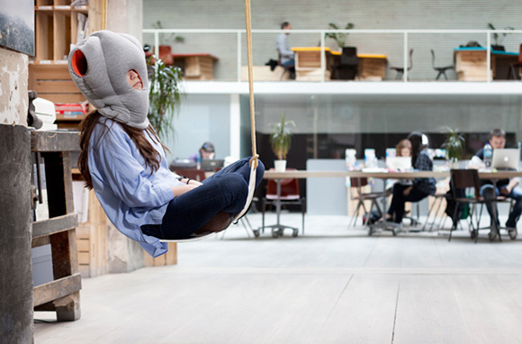 Woman sitting on a hammock using the Ostrich Pillow