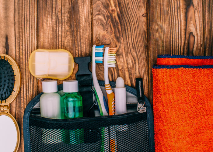 top view of a toiletry kit with toothbrush shampoo soap and towel