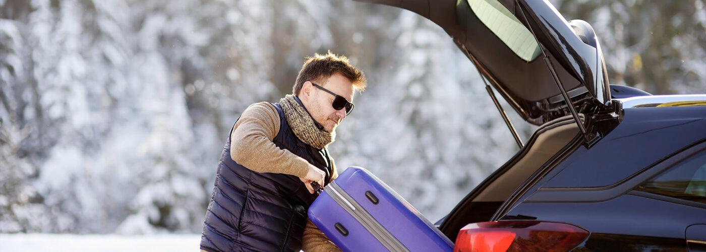man packing luggage in car road trip