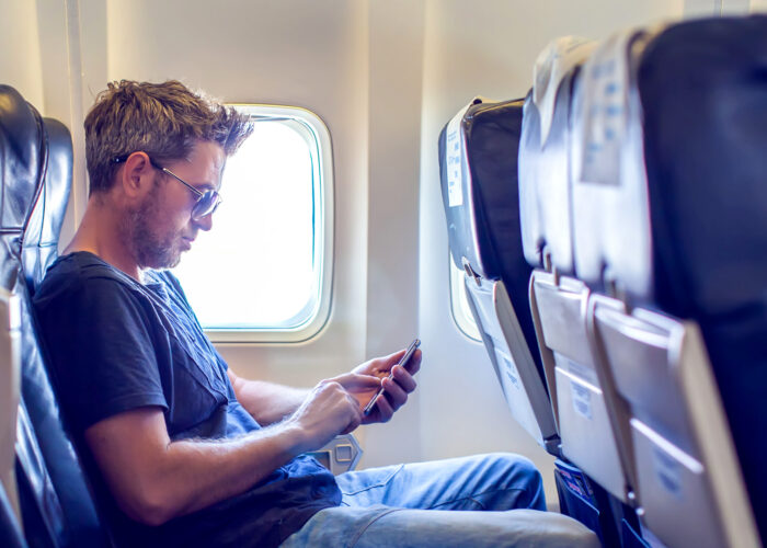 Man with dark hair is reading text message on mobile phone in airplane seat