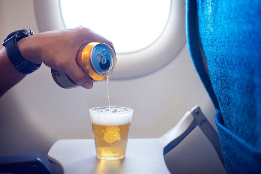 man pouring beer from can into a glass on airplane.