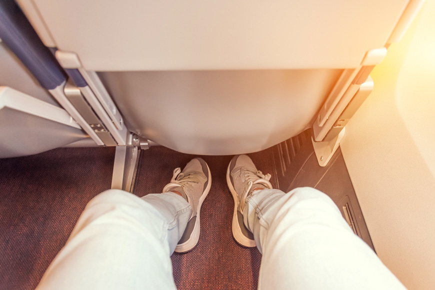 Enough legroom between the seats in the passenger plane, the view of the men's legs.