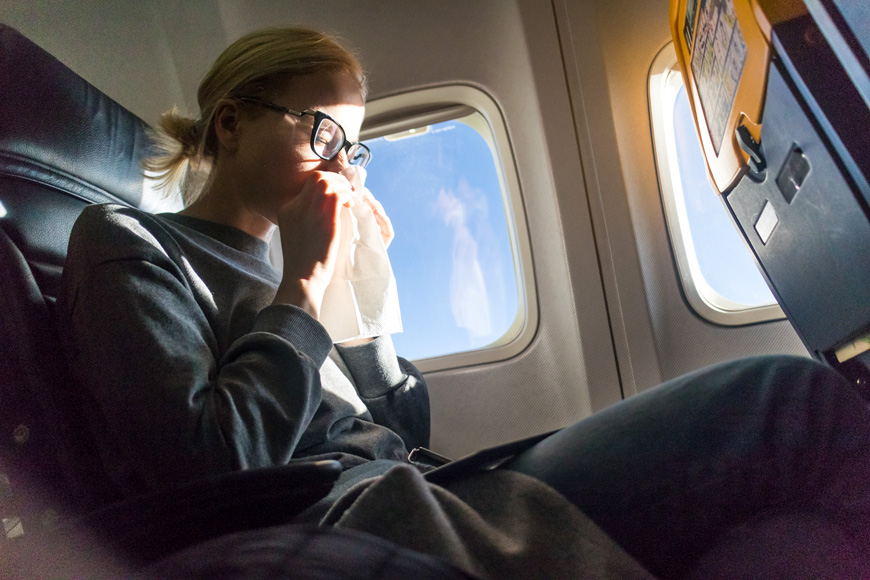 Blonde caucasian woman sneezing while flying by commercial airplane.
