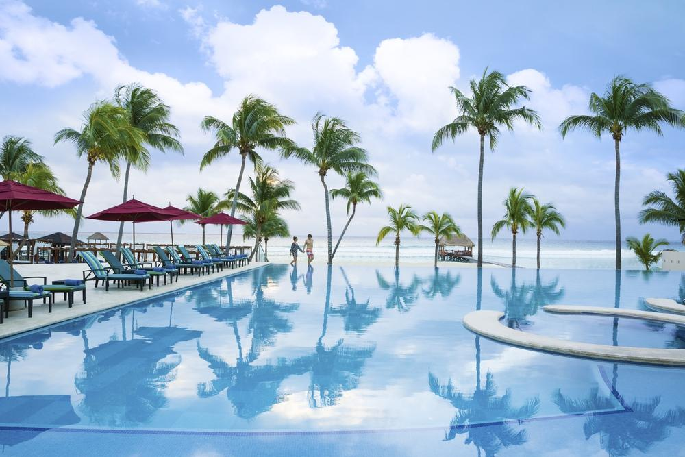 hotel pool with beach view and palm trees