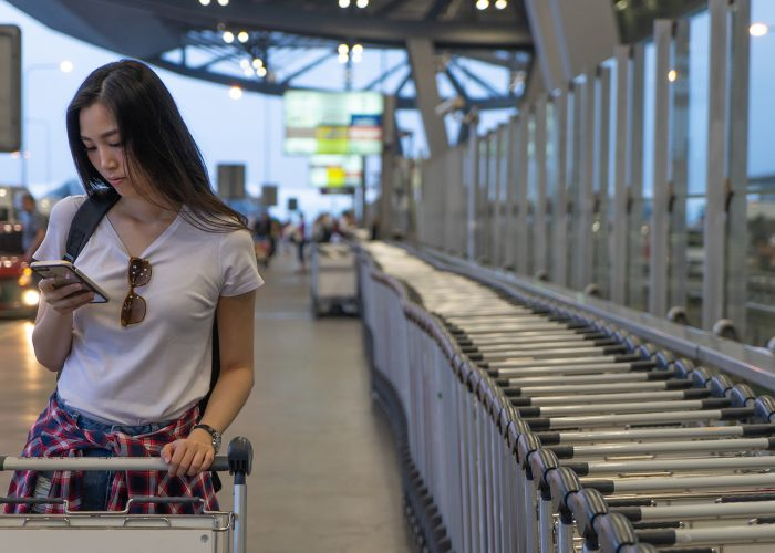woman on phone at airport with luggage trolley