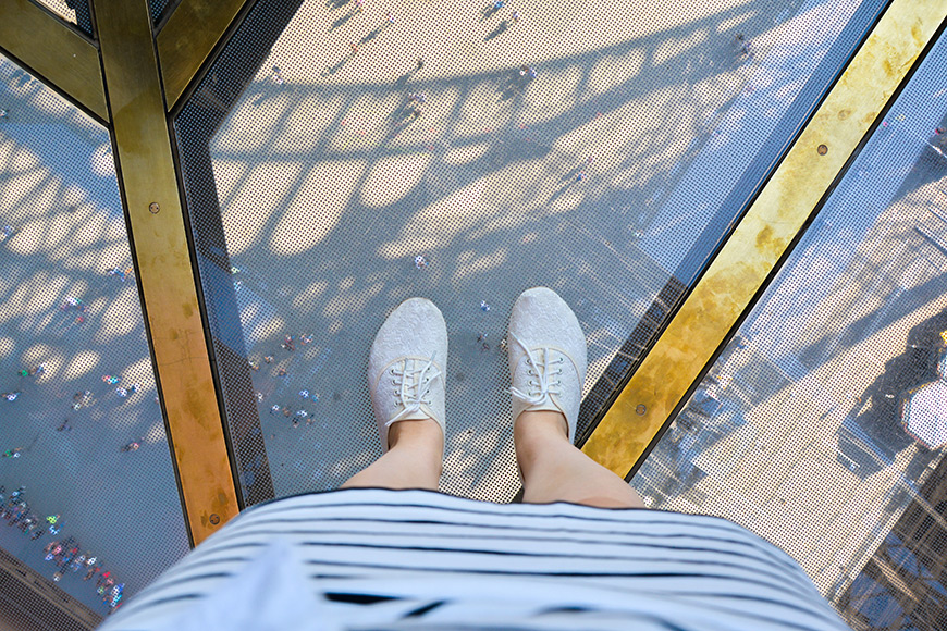 legs in white sneakers (shoes) and a skirt on glass floor eiffel tower.