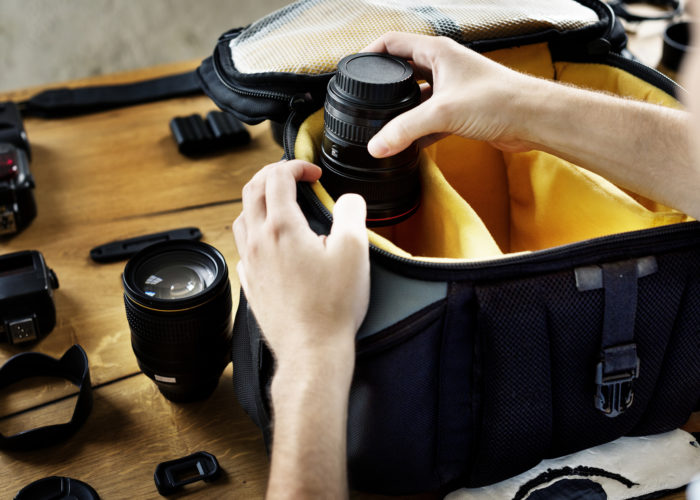 Person packing a camera bag with several lenses