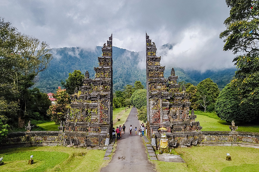 tourists walk through the gate of a hindu temple in bali