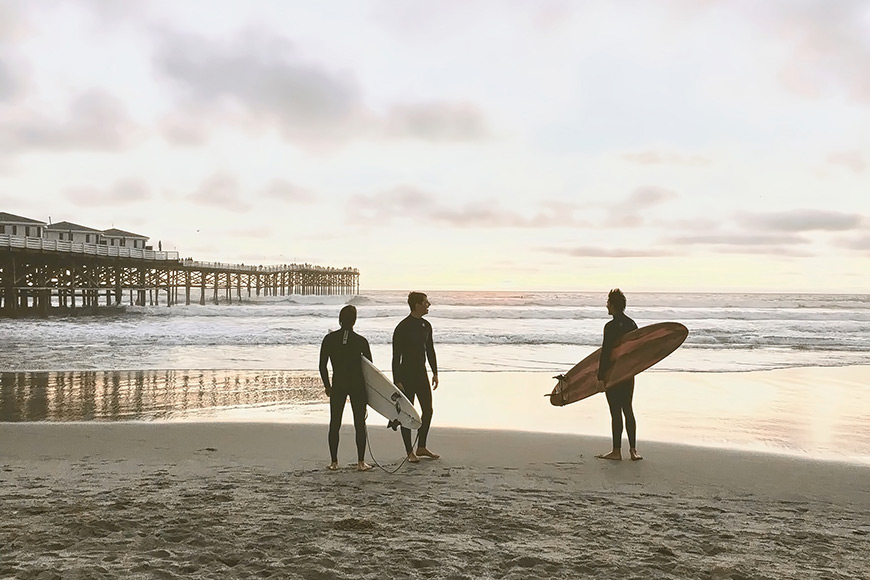 three men surfing in san diego california