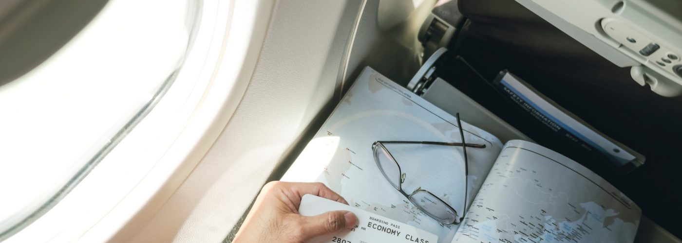 top-view-of-passenger-holding-boarding-pass-with-map-in-his-seat-on-board-an-airplane