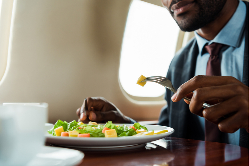 Man eating salad on plane