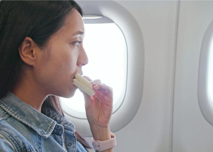Woman eating sandwich on plane.