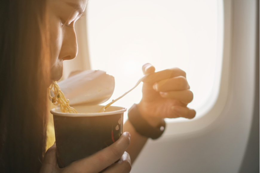 woman eating noodles on a plane.