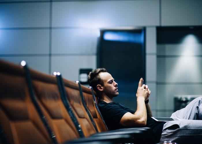 man using phone in airport