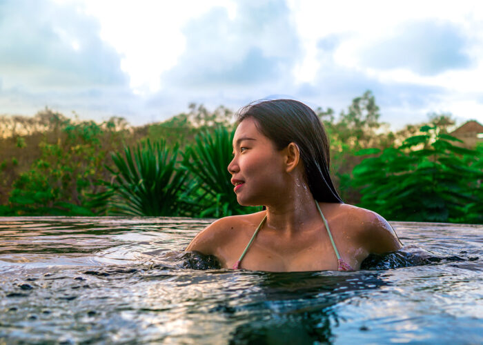 woman infinity pool tropical vacation