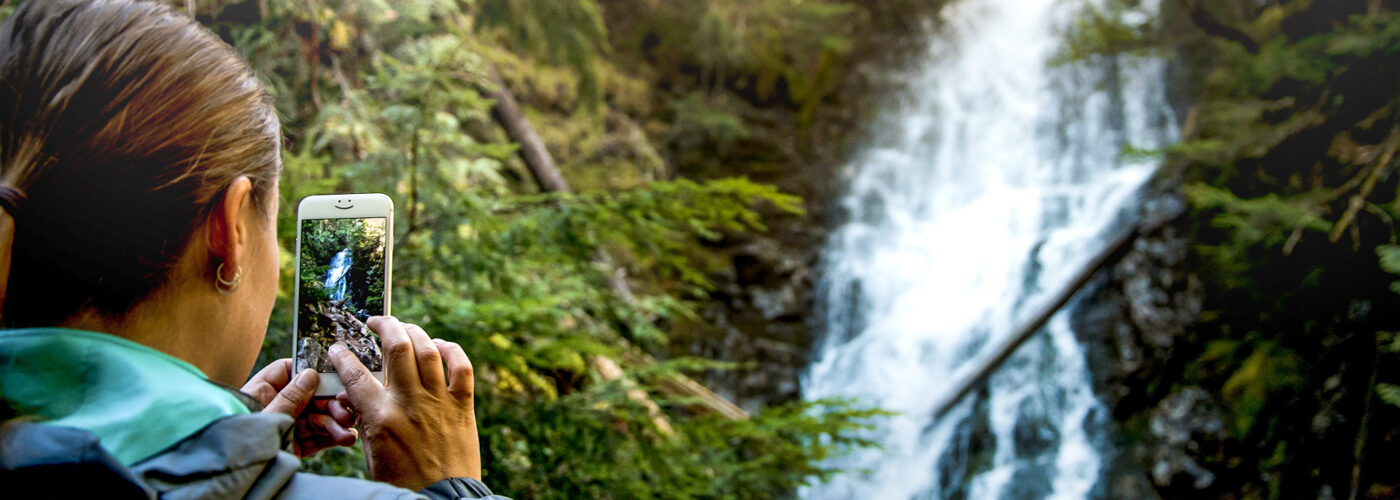 person taking photo or video of waterfall smartphone iphone