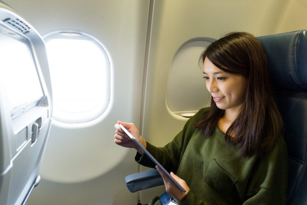 woman mobile device airplane seat