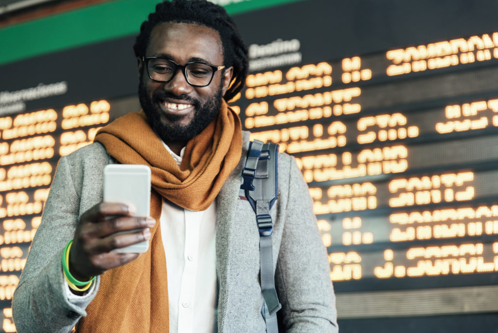 Man on cellphone in front of departures board