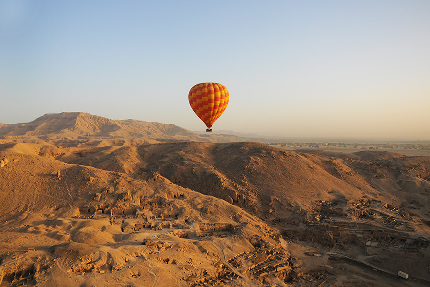 Orange hot air balloon riding over the desert and ruins in Luxor Egypt