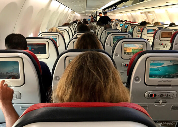 airplane cabin woman in middle seat.
