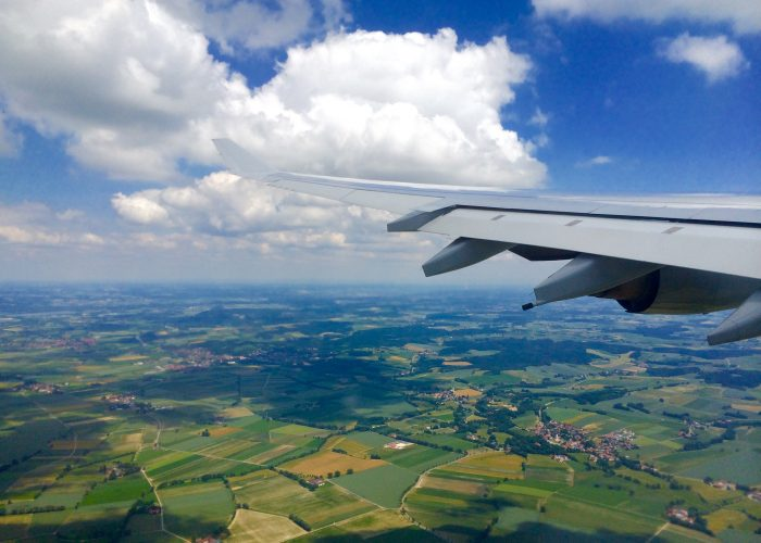 airplane wing over green landscape.