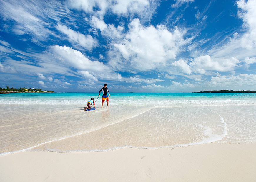 father and child on beach in bahamas
