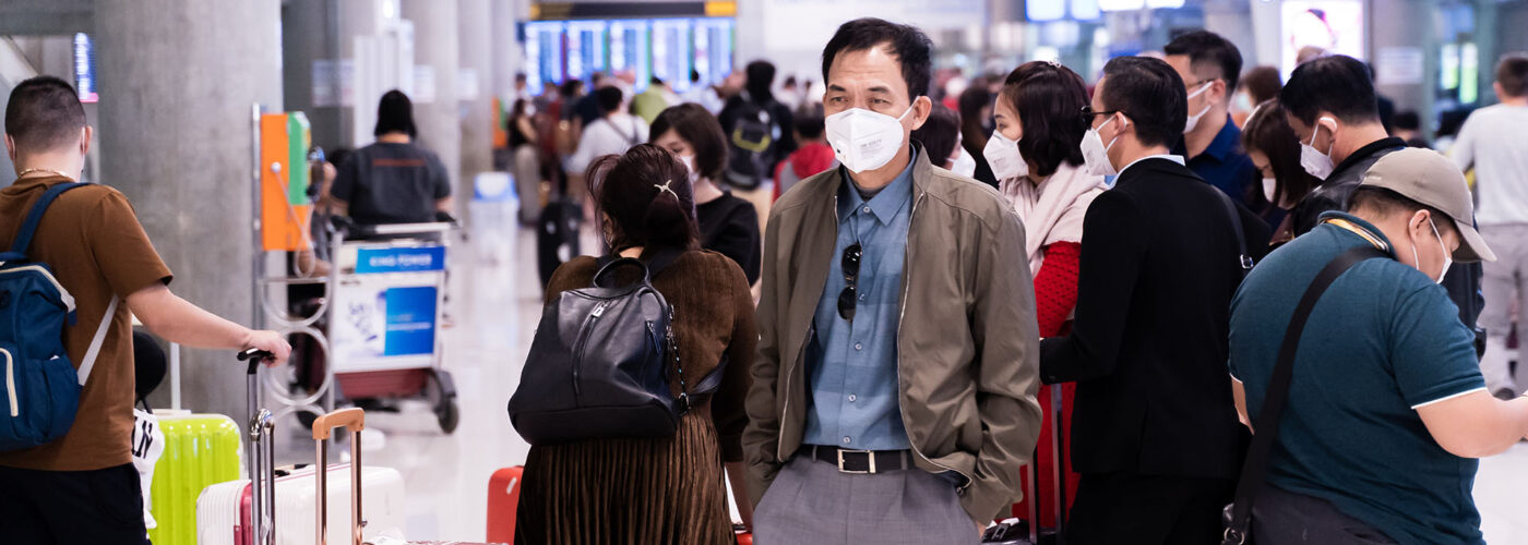 man in mask at crowded airport.