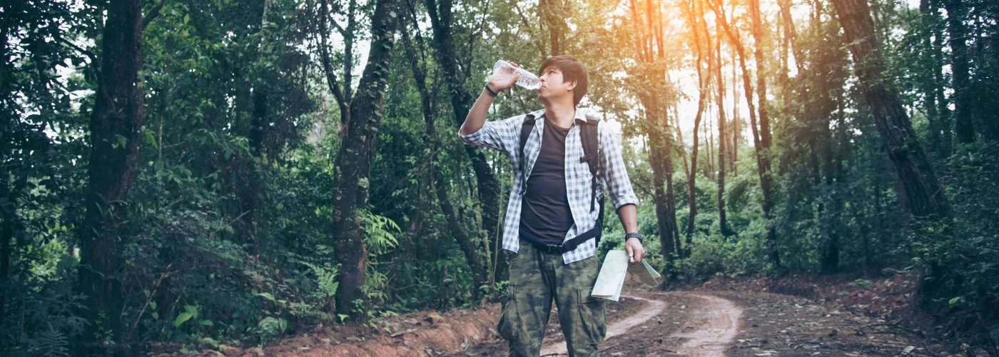 hiker drinking water in the woods