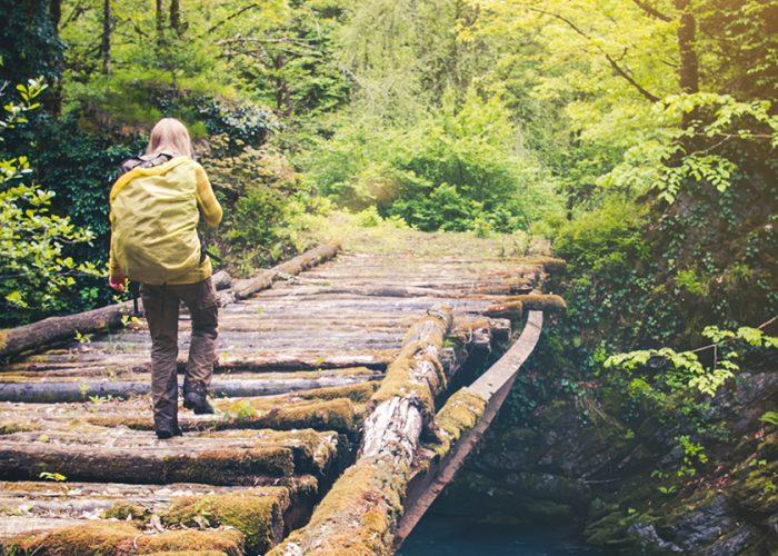 woman hiking on bridge