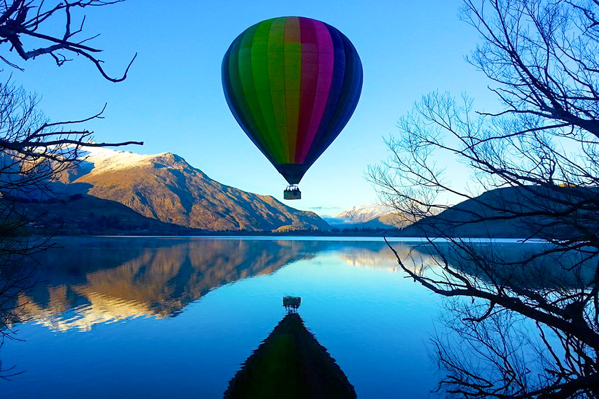 hot air balloon over lake in queenstown new zealand