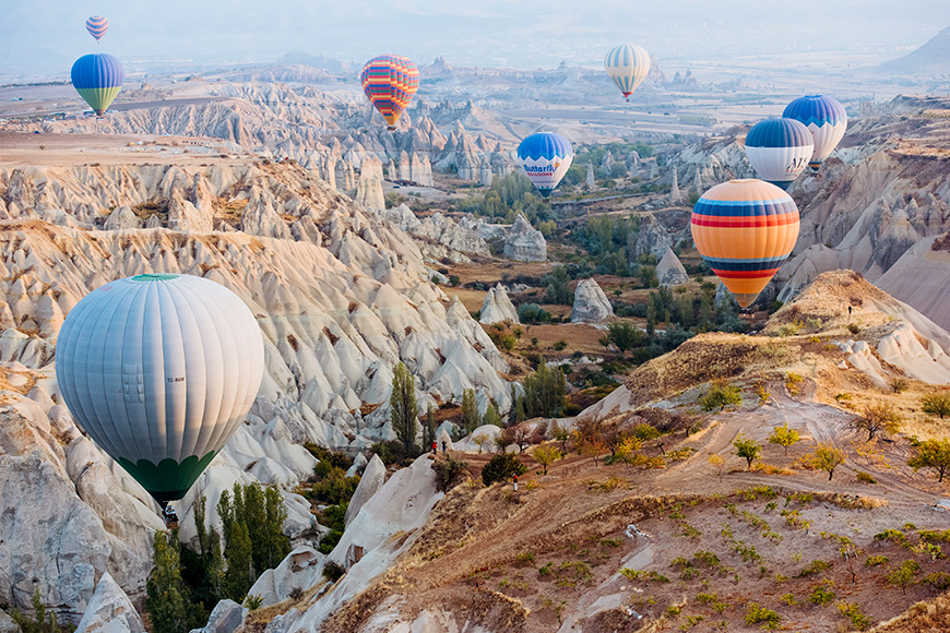 view of hot air balloons flying over the Valley of Love in Cappadocia