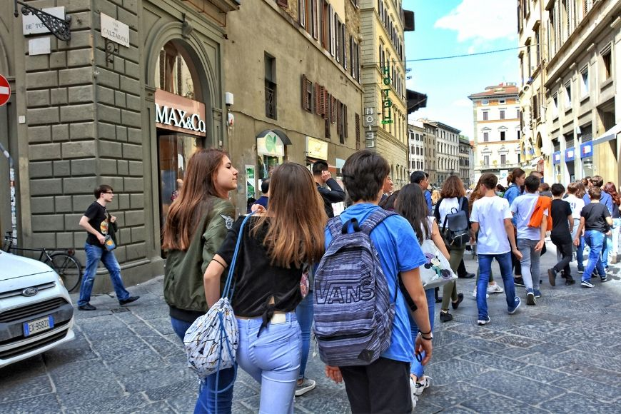 tourists with backpack and large purse in crowd.